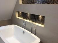 mozaikos falfülkével dekorált modern fürdő íves káddal